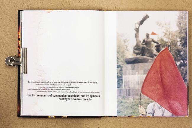 Aufgeschlagenes Buch mit Text und Fotografie einer roten Fahne vor einer Statue