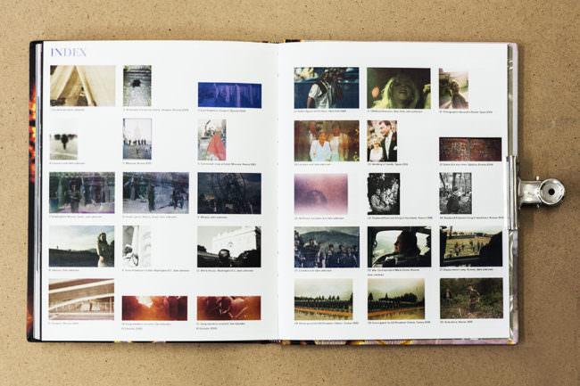 Aufgeschlagenes Buch mit Doppelseite voller farbiger Indexfotografien