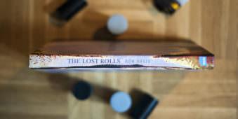 Buchrücken Abbildung von The Lost Rolls mit Filmdosen dekoriert auf Holzfußboden