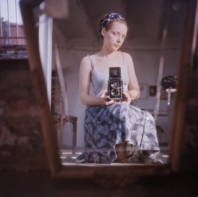 Eine Frau schaut in den Spiegel und fotografiert sich selbst.