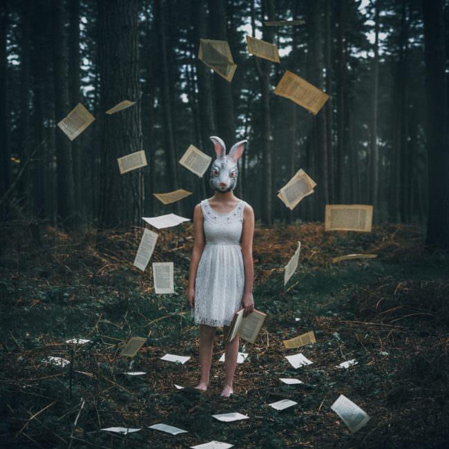 Eine Frau mit Hasenmaske zwischen fliegenden Büchern