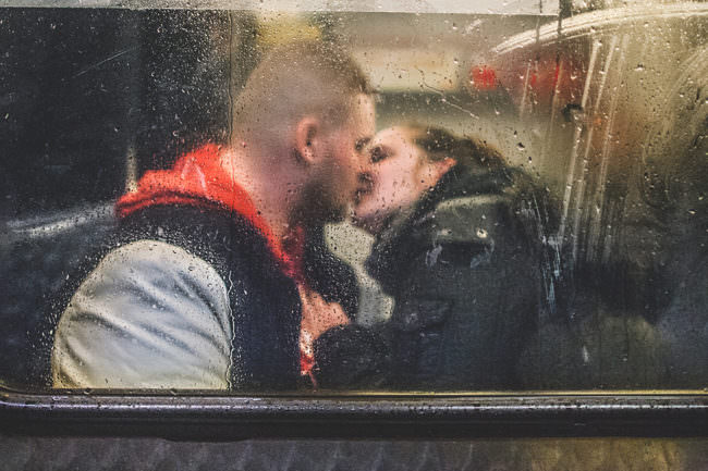 Zwei Menschen küssen sich hinter einer verregneten Scheibe