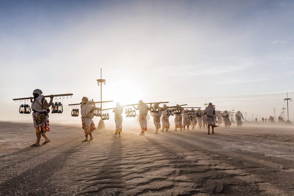 Beduinen in der Wüste tragen etwas.