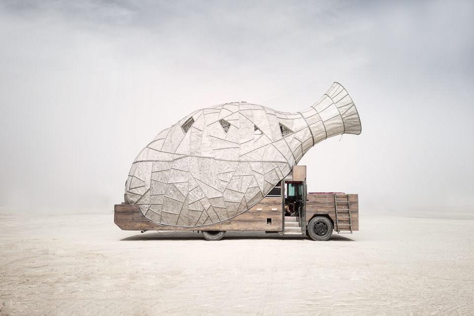 Eine riesige Papierflasche auf einem Fahrzeug.