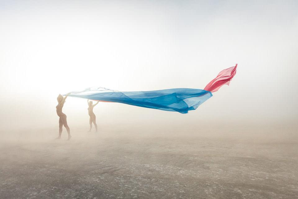 Frauen halten ein Tuch in den Wind.