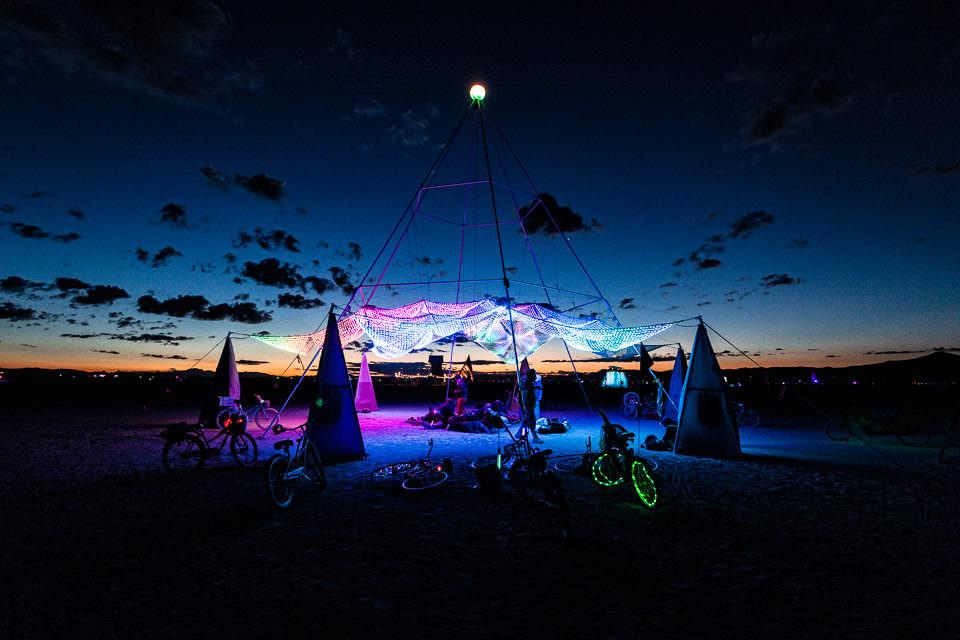 Licht in der Nacht und Menschen unter einem Zelt.