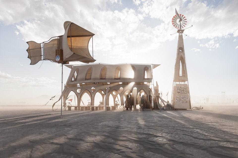 Ein Gebäude und ein Windrad in der Wüste.