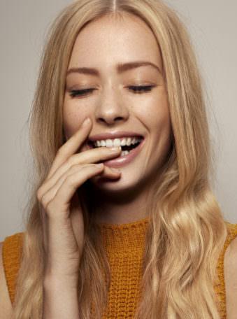 Lachende Frau beißt sich auf den Finger