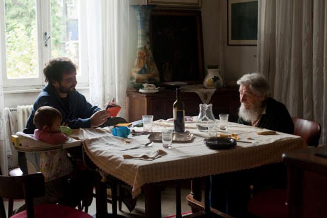 Ein alter Mann, ein junger Mann und ein kleines Kind sitzen an einem Tisch.