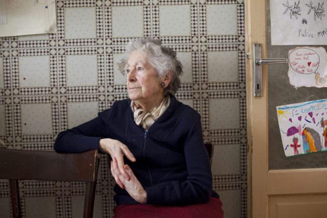 Eine ältere Dame sitzt auf einem Stuhl.