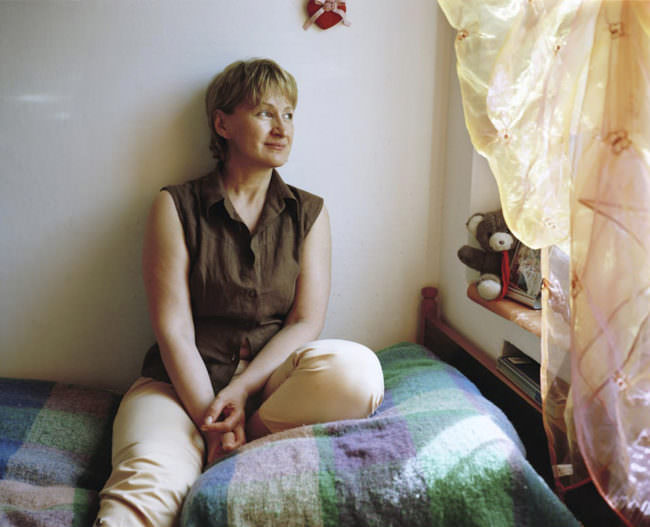 Eine Frau sitzt auf einem Bett und schaut aus dem Fenster.