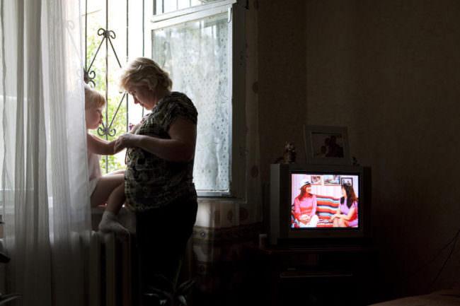 Eine Frau und ein Mädchen am Fenster, es läuft ein Fernseher.