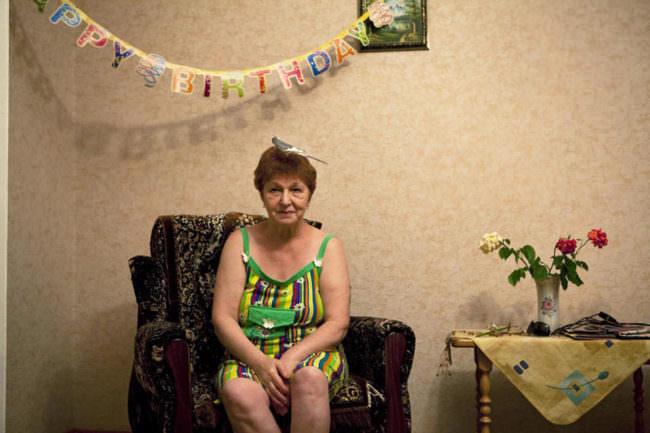 Eine Frau sitzt auf einem Stuhl, auf ihrem Kopf ein Papagei und über ihr eine Geburtstagsgirlande.