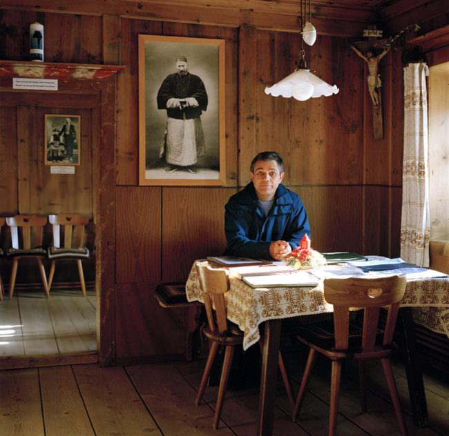 Ein Mann sitzt an einem sonnenbeschienenen Tisch, hinter him ein Heiligenportrait.