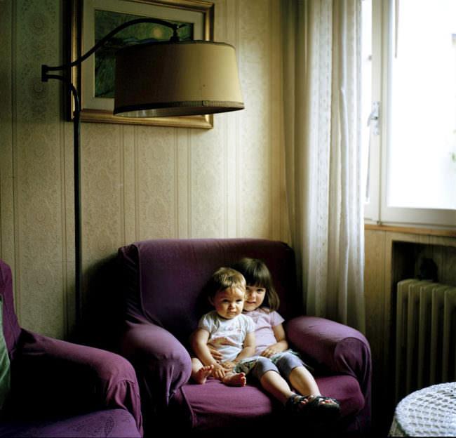 Zwei Kinder sitzen auf einem Sessel.