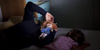 Ein Erwachsener und ein Kind liegen auf einem Bett, der Erwachsene hält sich eine rothaarige Puppe vors Gesicht.