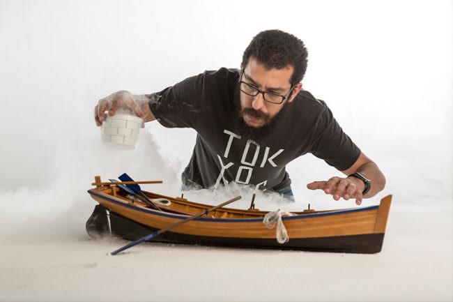 Ein Mann macht Nebel über einem Miniaturboot