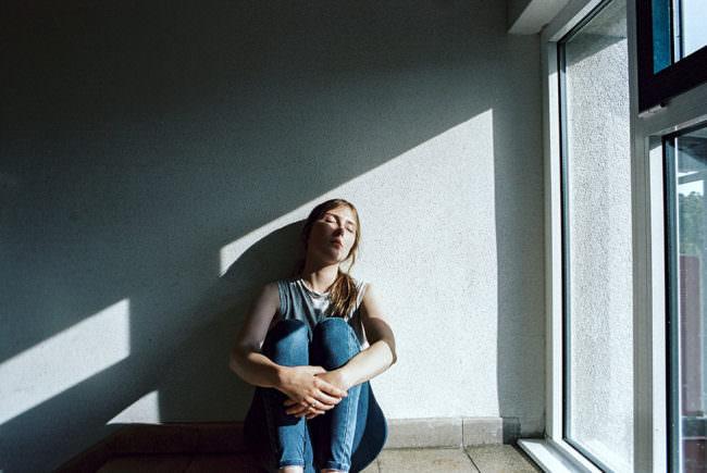 Frau am Fenster im Lichtschein