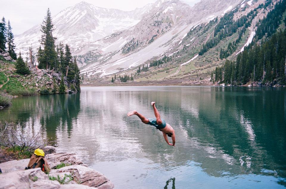 Ein Mensch springt kopfüber in einen Bergsee