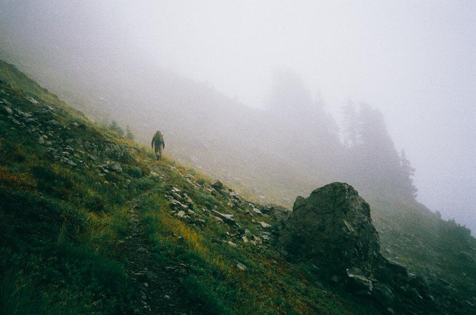 Ein Mensch bewegt sich einen nebelverhangenen Abhang hinauf