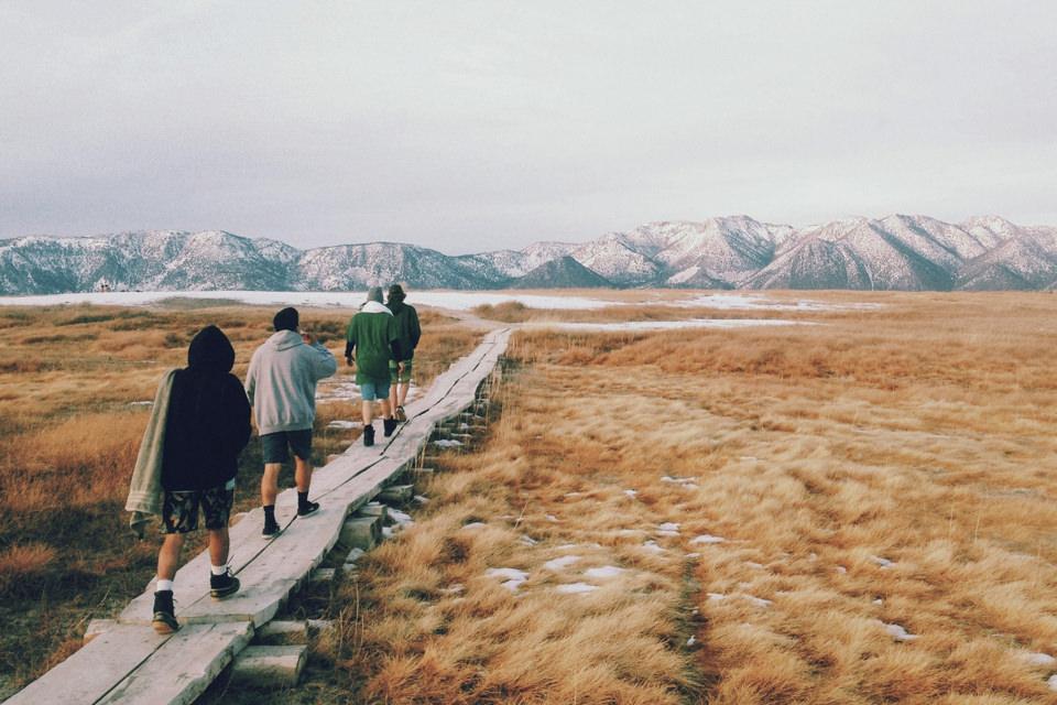 Vier Menschen gehen einen Steg entlang