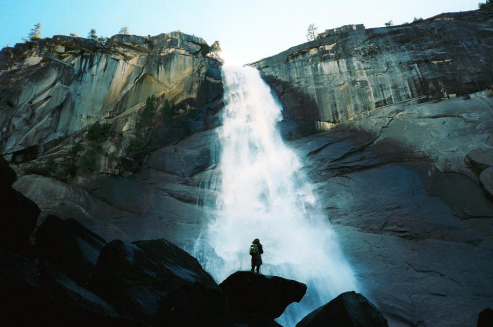 Ein Mensch steht vor einem Wasserfall