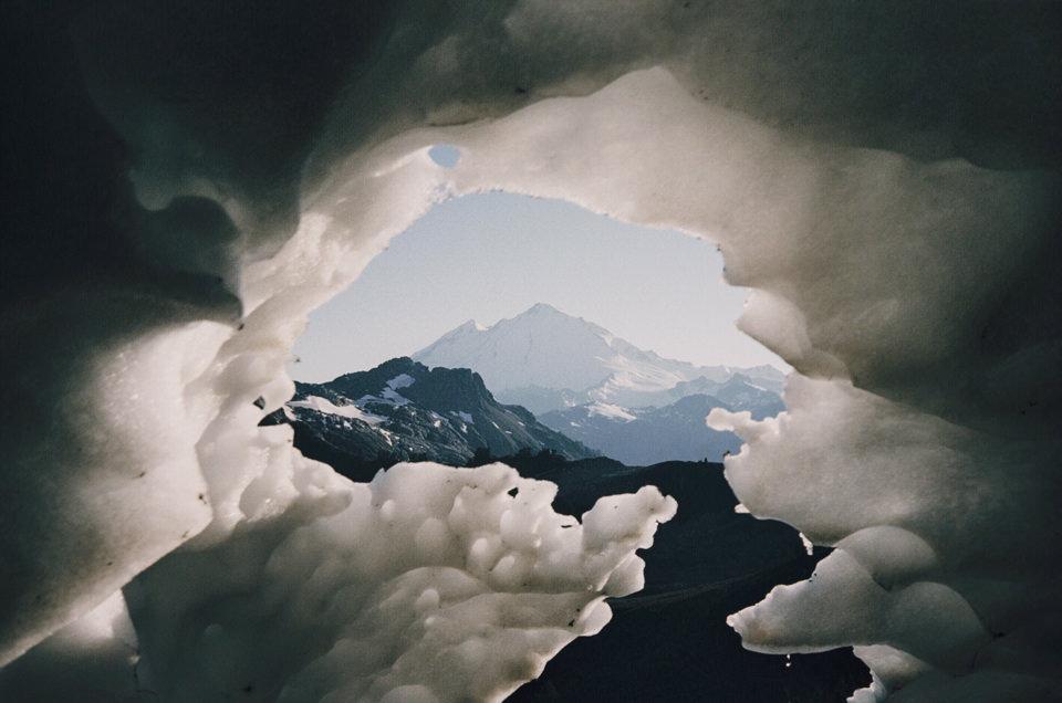 Blick durch ein Loch im Eis auf Berge