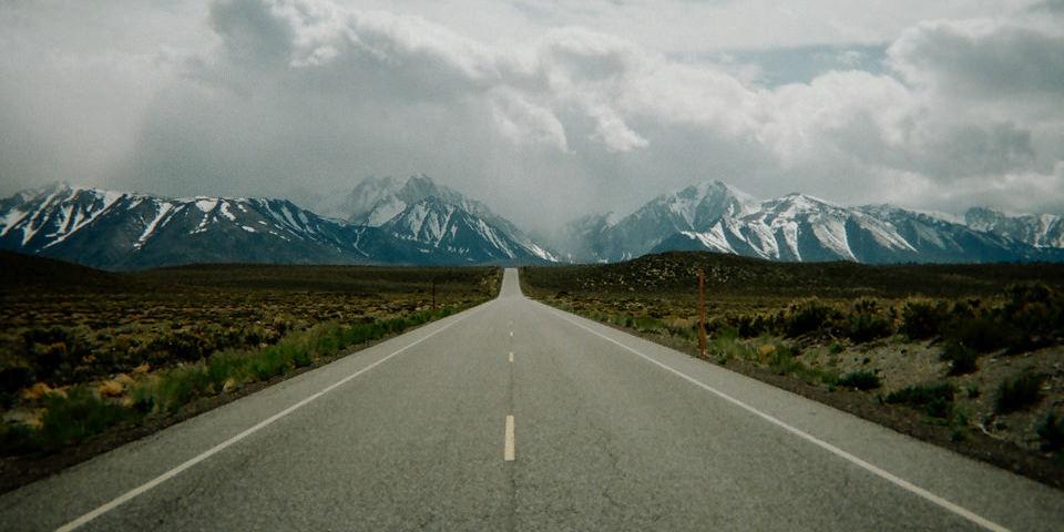 Eine Straße führt auf Berge und Wolken am Horizont zu