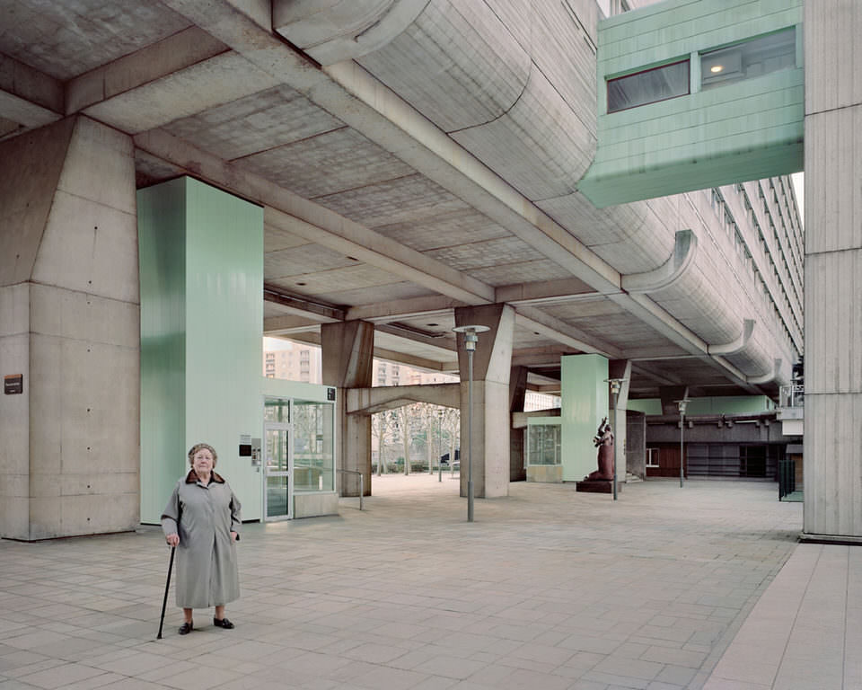 Eine ältere Frau mit Stock in einem Betontunnel