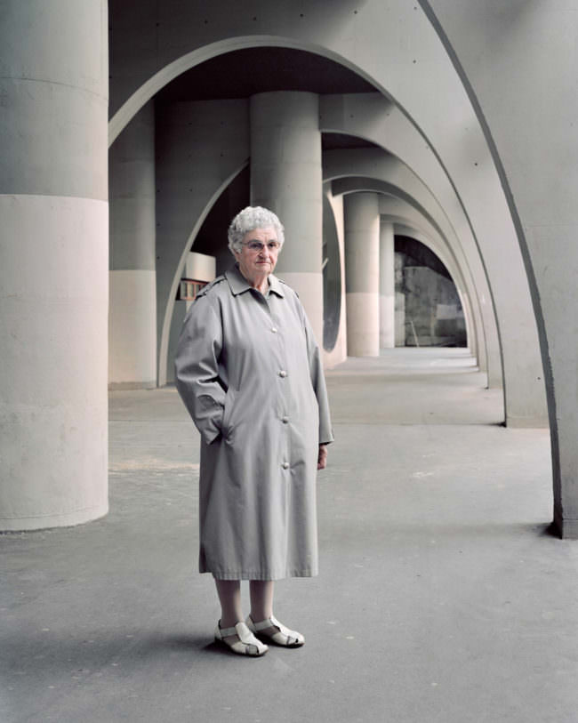 Frau mit grauer Jacke in Betondurchgang