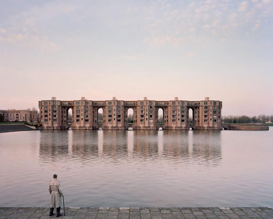 Mann sieht über den Fluss auf eine Häuserfront