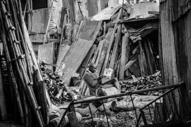 Ein Mann sitzt inmitten von Wellblechwänden und Holzbrettern und liest eine Zeitung