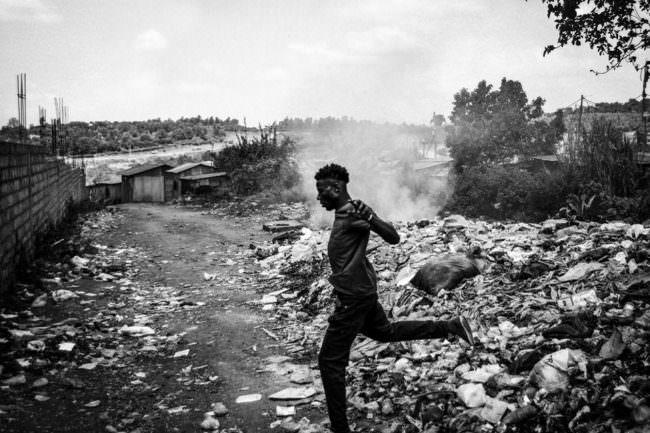 Ein Mann springt über einen Müllberg