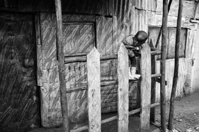 Ein Kind beugt sich über einen Zaun