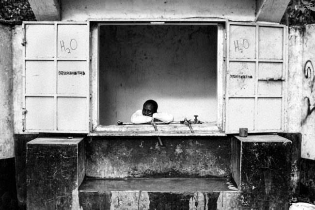 Ein Mensch schaut aus einem geöffneten Fenster, den Kopf auf die Arme abgelegt