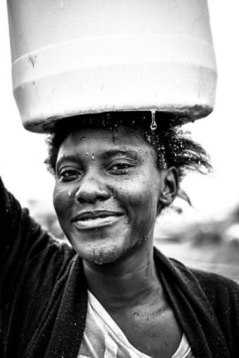 Portrait einer Frau mit einem Wasserkanister auf dem Kopf