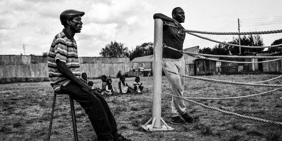 Zwei Männer an einem Boxring, im Hintergrund eine Gruppe Kinder