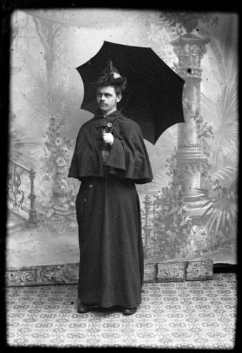 Ein Mann in antiken Frauenkleidern mit Schirm
