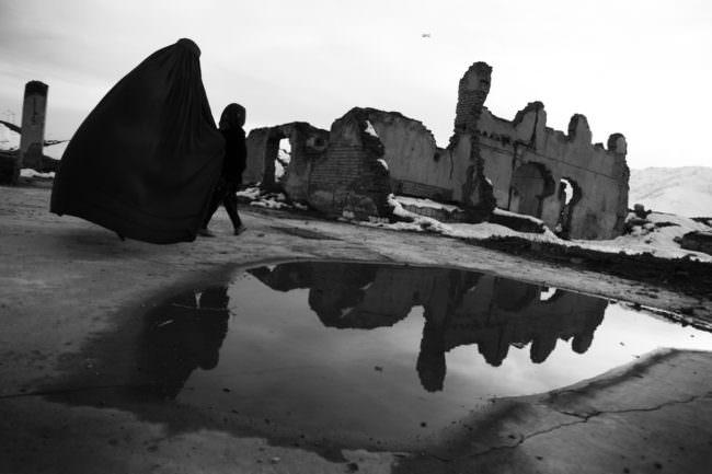 Frau mit Kind vor einer Ruine und Wasserlage