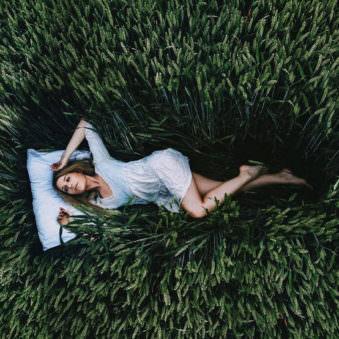 Eine Frau mit Kopfkissen im Gras