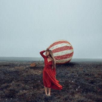 Eine Frau im roten Kleid vor einem Ballon