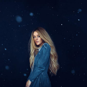 Eine Frau mit langen Haaren vor blauem Hintergrund