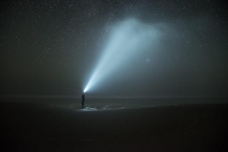 Stirnlampe erhellt den Nachthimmel