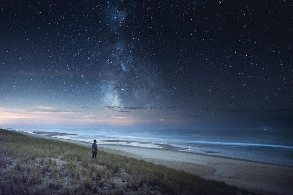 Person am Strand mit Blick auf die Milchstraße