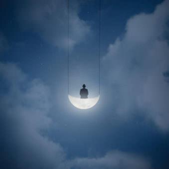 Man sitzt auf einer Mondschaukel