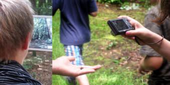 Hinterkopf eines jungen mit Tablett im Wald und Kinder die etwas auf einer Hand fotografieren.