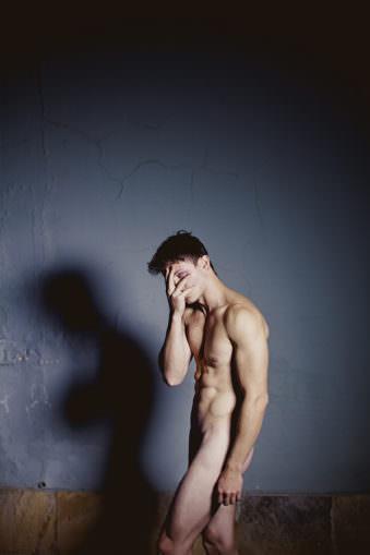 Nackter Mann stehend, bedeckt mit der Hand sein Gesicht und blickt durch die Finger.