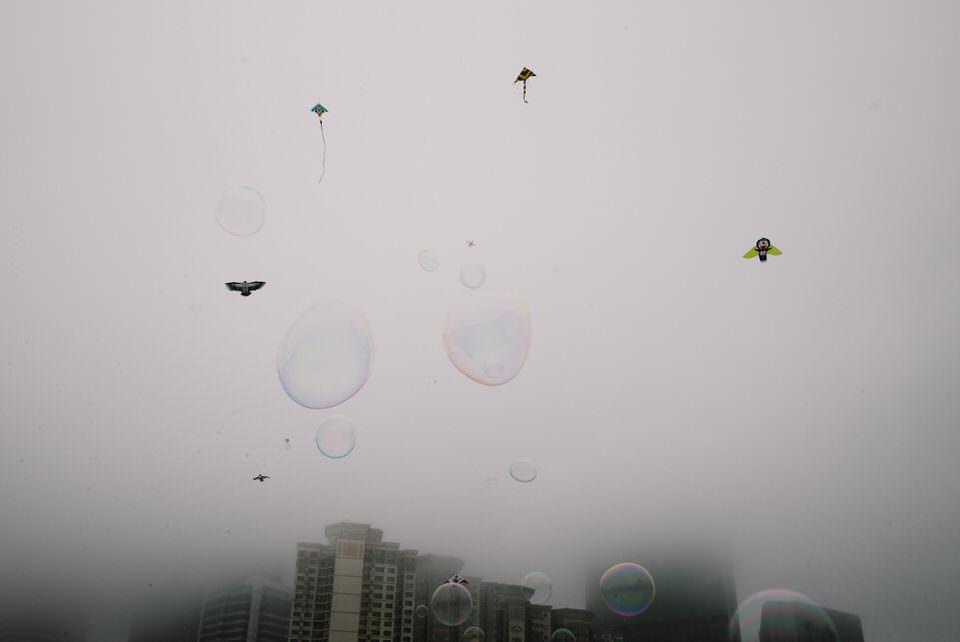 Seifenblasen und Drachen im Nebel vor Hochhäusern