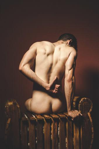 Nackter Mann sitzt mit dem Rücken zum Betrachter auf Rattanmöbel und zeigt einen Daumen hoch.