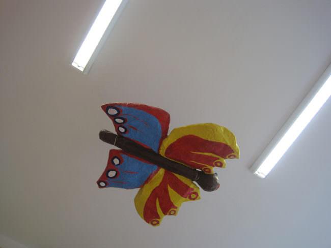 Schmetterling aus Papier in bunt fliegend mit 2 Neonröhren.